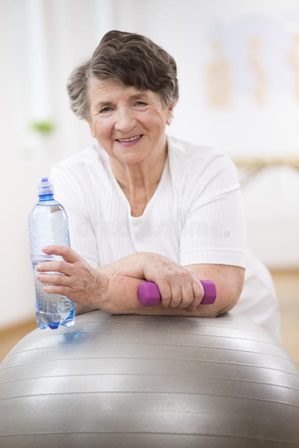 Senior woman with water bottle and dumbbell leaning on grey gymnastic ball. Senior woman with water bottle and dumbbell leaning on gymnastic ball royalty free stock photo