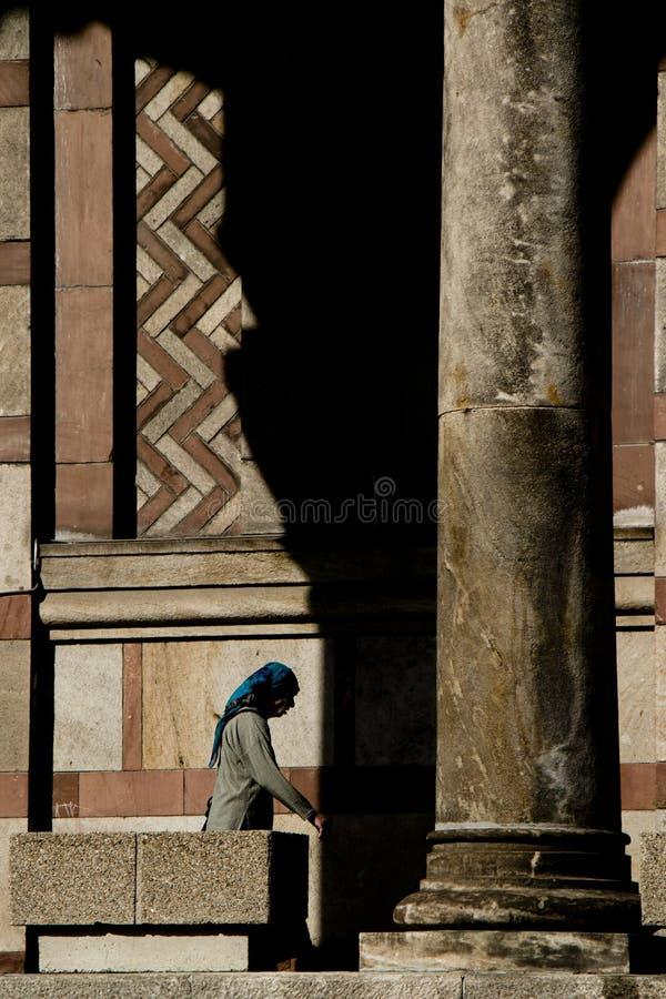 Senior woman wearing blue scarf walking in the arcade of Saint Mark`s orthodox church stock photos