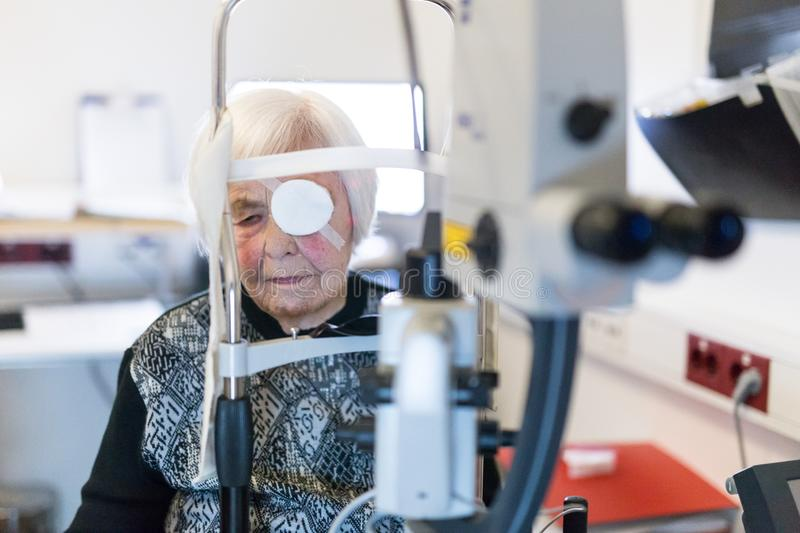 Senior woman wearing eye pathc after laser surgery procedure at ophthalmology clinic. Elderly 95 years old woman wearing eye pathc after laser surgery procedure royalty free stock photography