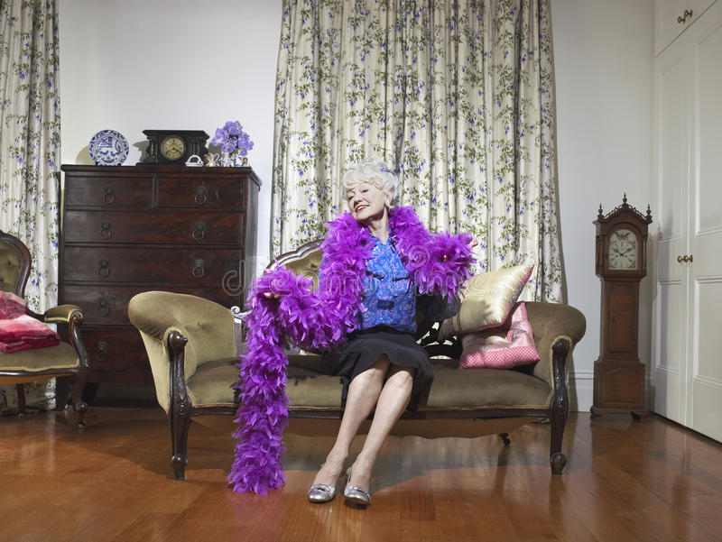 Senior Woman Wearing Feather Boa In Living Room stock photography