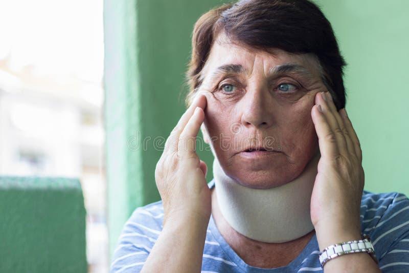 Senior woman wearing neck brace. Senior woman has emotional stress stock image