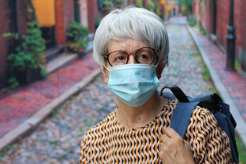 Senior woman wearing surgical mask outdoors royalty free stock images