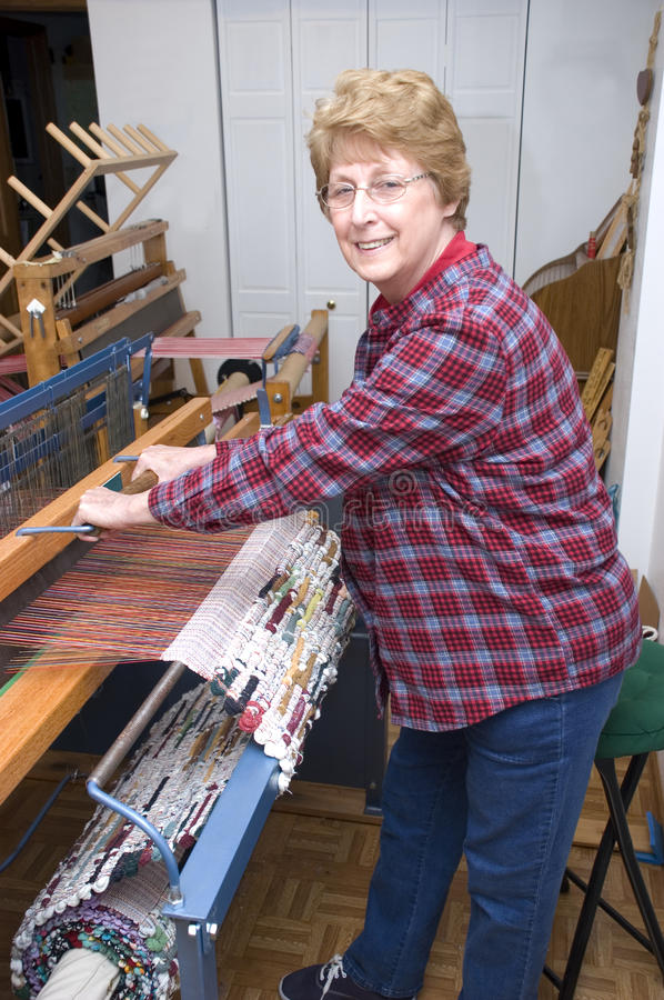 Senior Woman Weaving on Loom, Textile Artist. Active senior woman works on her loom to produce textile arts and weaving products stock images
