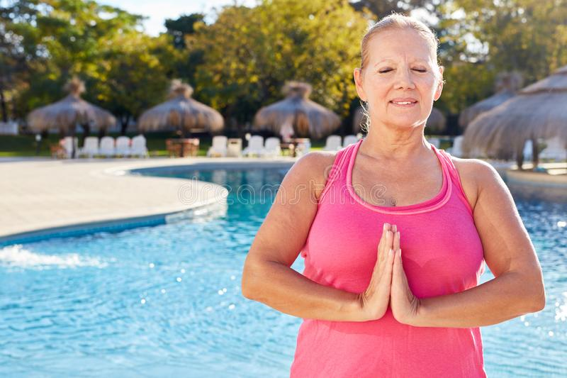 Senior woman at the wellness pool folds her hands during yoga meditation stock photo