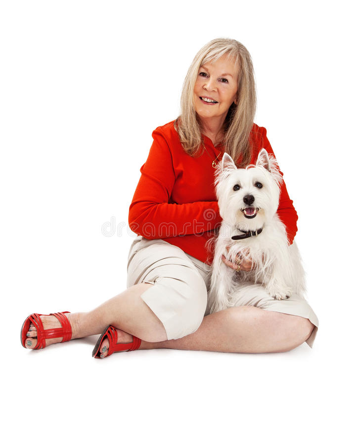 Senior Woman With West Highland Dog. An attractive mature woman sitting and holding a cute white West Highland terrier dog royalty free stock photo