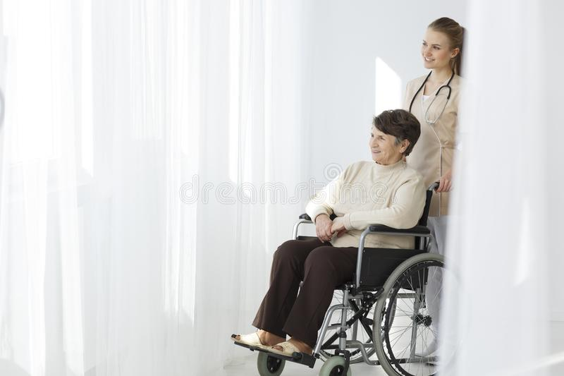 Senior woman on wheelchair and caregiver. Smiling senior women sitting on wheelchair and young caregiver standing behind her stock photo