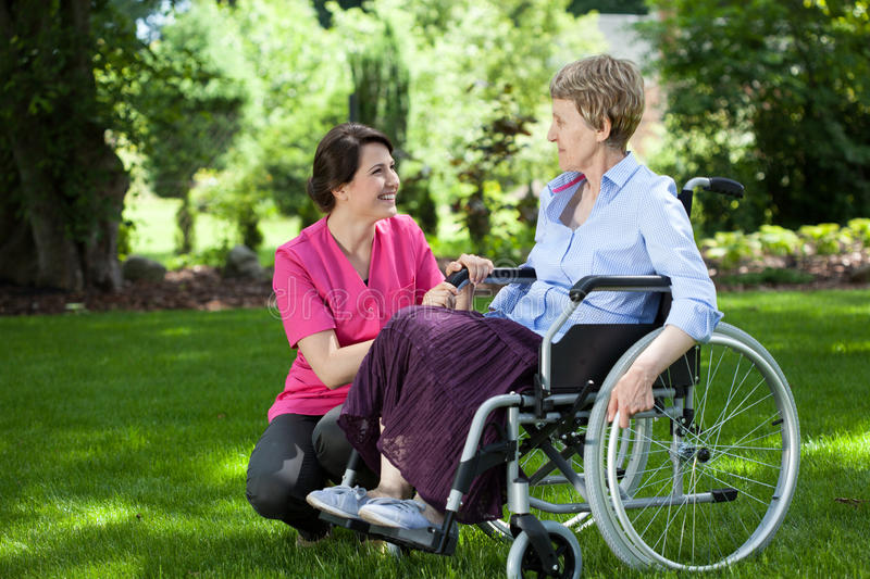 Senior woman on wheelchair with caring caregiver. Happy senior women on wheelchair with caring caregiver outdoors royalty free stock photo