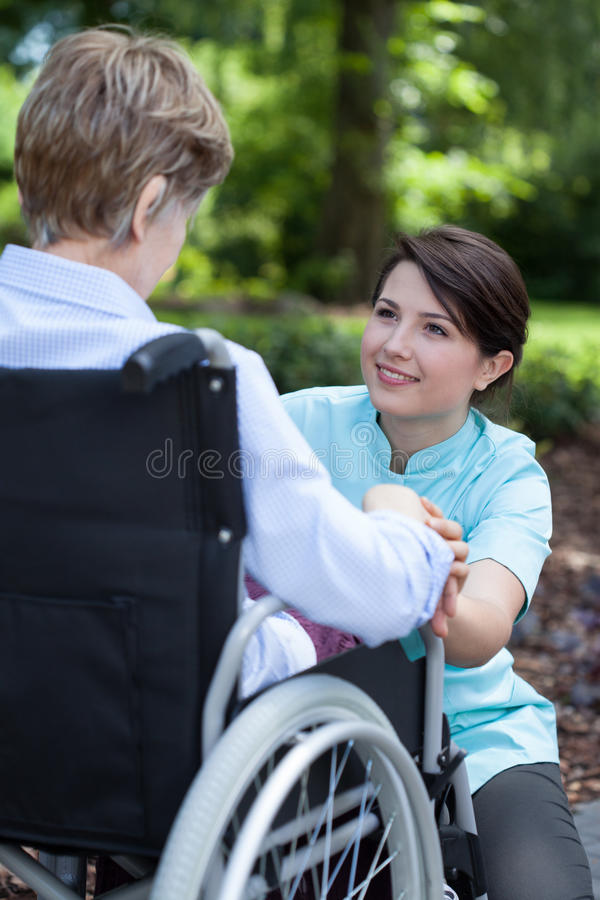Senior woman on wheelchair with her caregiver stock photos