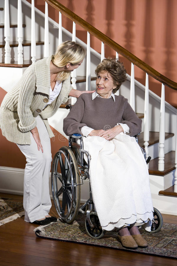Senior woman in wheelchair with nurse helping. Senior woman in wheelchair talking with nurse at home royalty free stock images