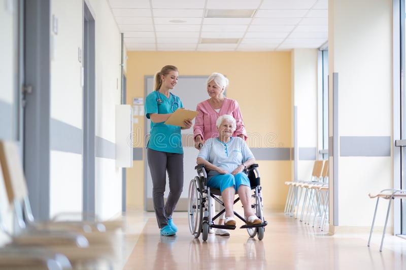 Senior woman in wheelchair with nurse in hospital stock images