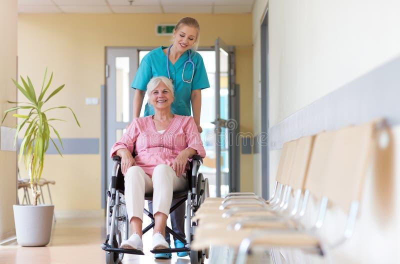 Senior woman in wheelchair with nurse in hospital stock photos