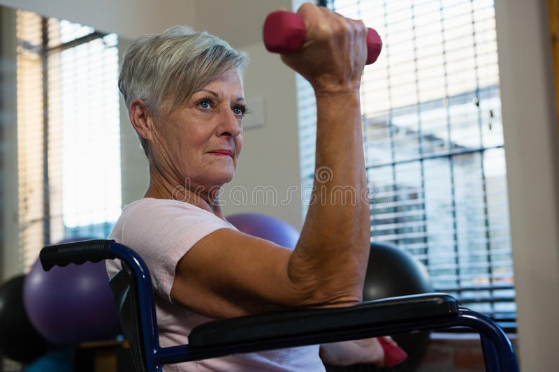 Senior woman in wheelchair performing exercise with dumbbell royalty free stock photos