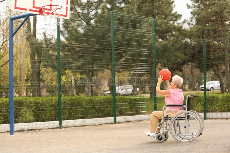 Senior woman in wheelchair playing basketball on  ground stock photos