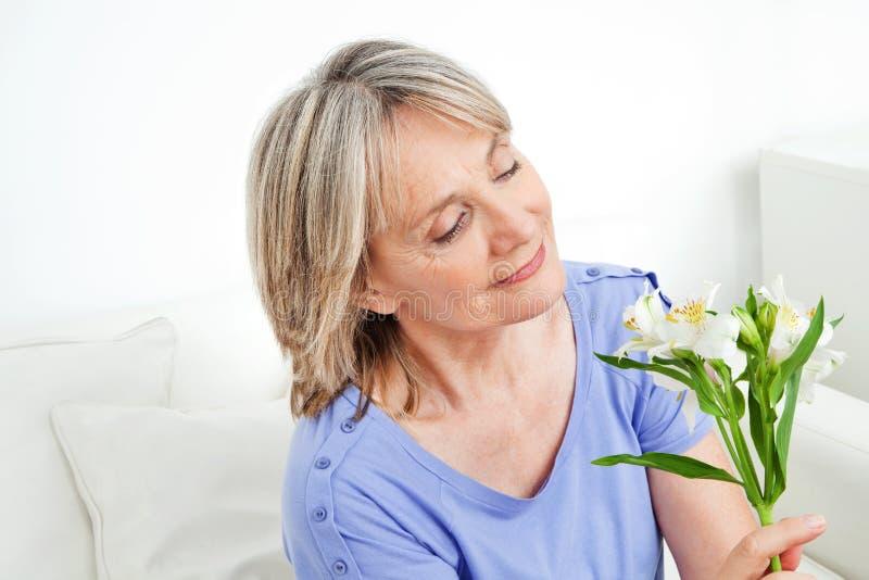 Senior woman with white lilies stock photos