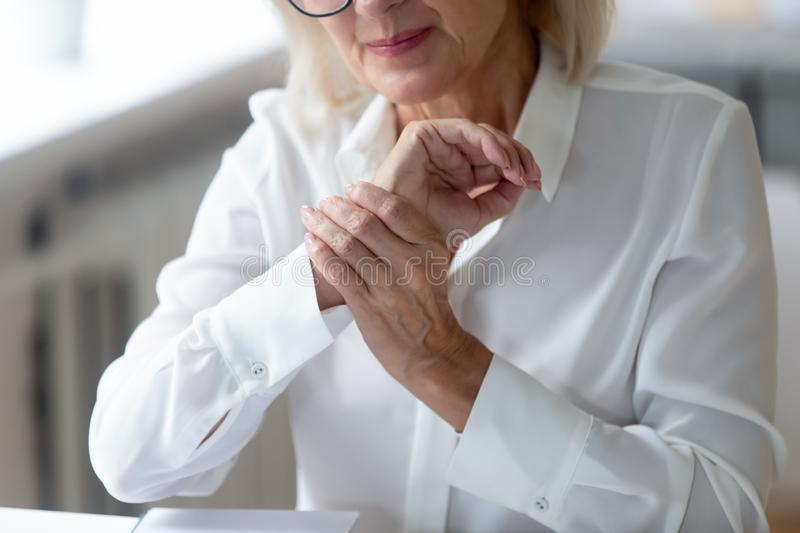 Senior woman worker suffering from wrist spasm or strain. Crop close up of distressed aged grey-haired woman worker touch massage wrist suffering from hand spasm stock photos