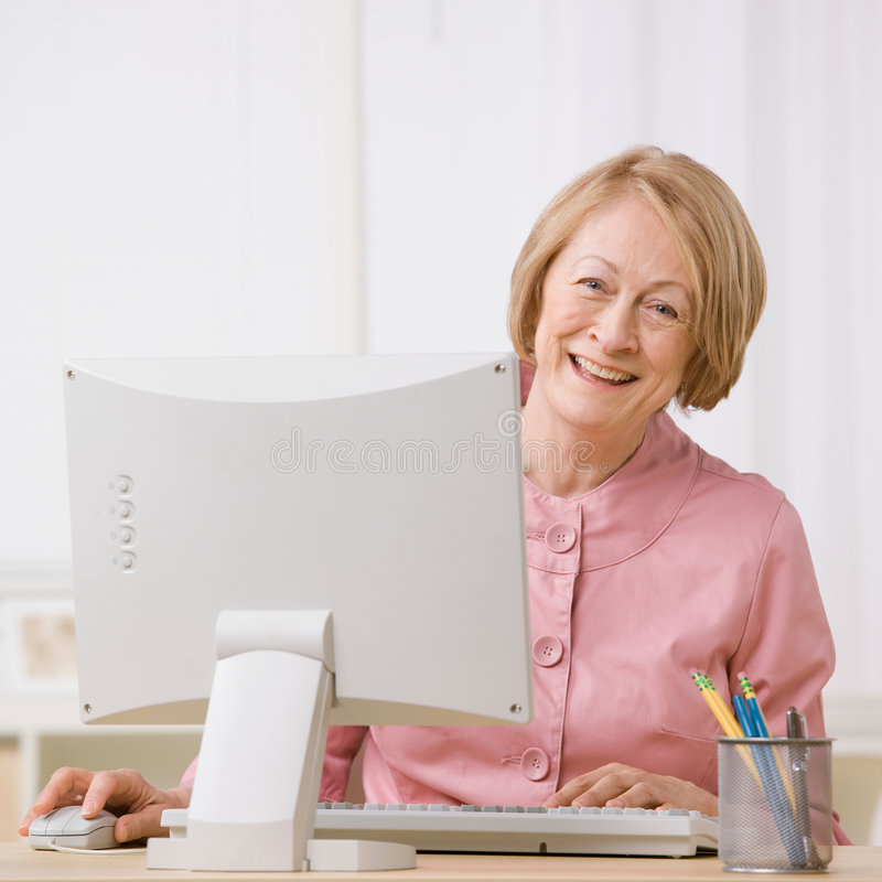 Senior woman working on computer at desk stock photos