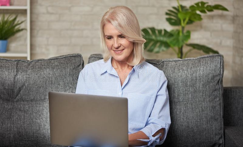Senior woman is working on her laptop computer. Sitting on a sofa at home stock photo