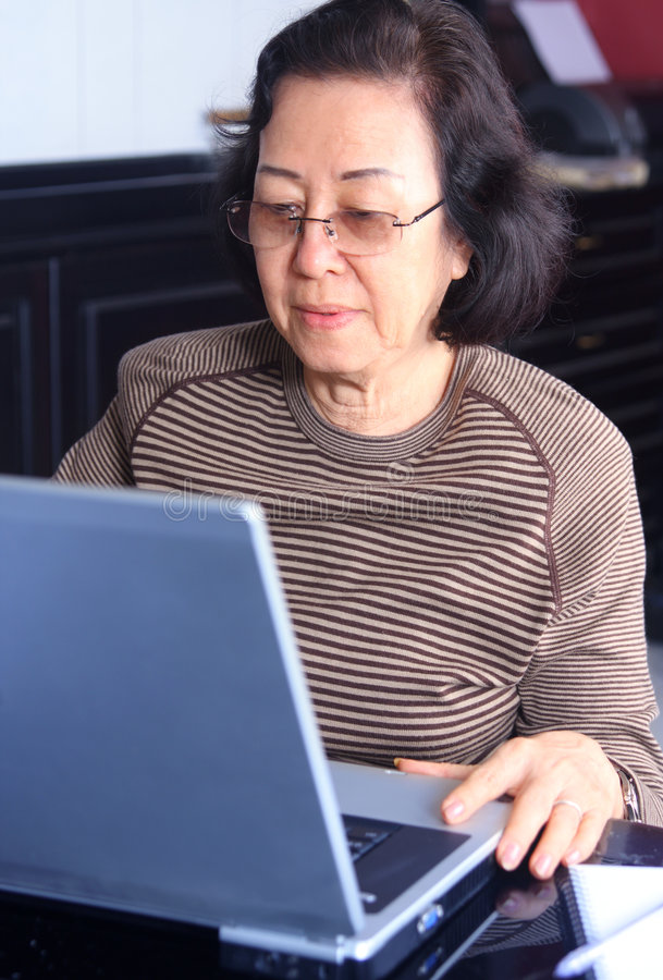 Senior woman working on a laptop stock photography
