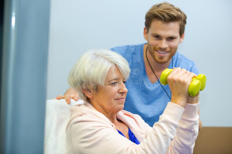 Senior woman working out with dumbbells with personal trainer stock image