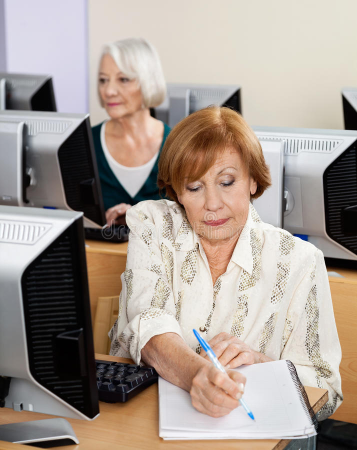 Senior Woman Writing Notes In Computer Class. Senior women writing notes at desk with classmate in background during computer class royalty free stock image