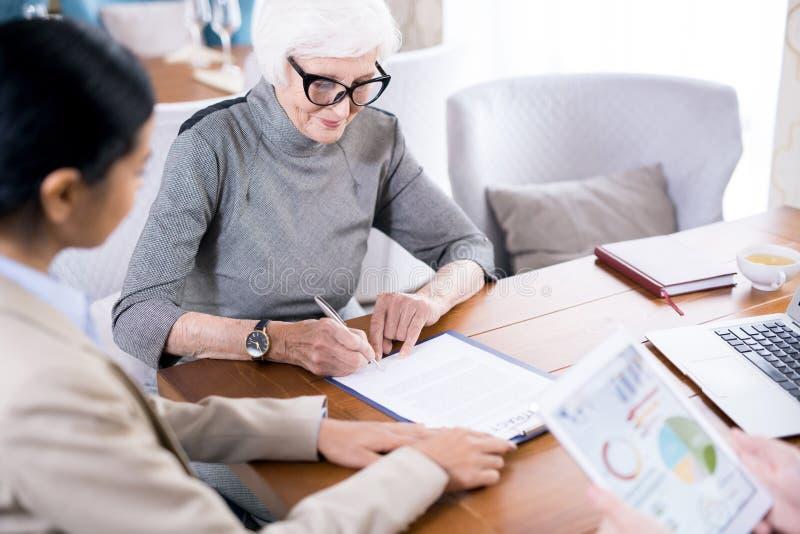 Senior woman writing testament stock image