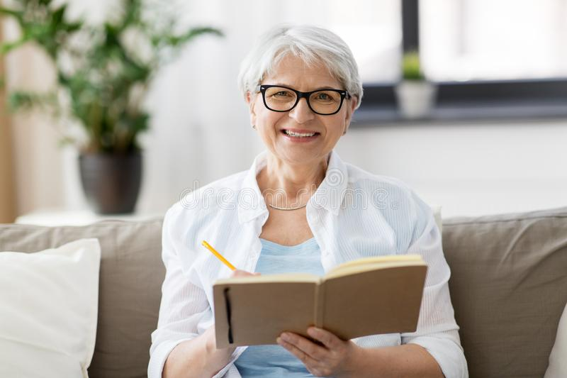Senior woman writing to notebook or diary at home. Age, leisure and people concept - happy senior woman in glasses writing to notebook or diary at home royalty free stock image