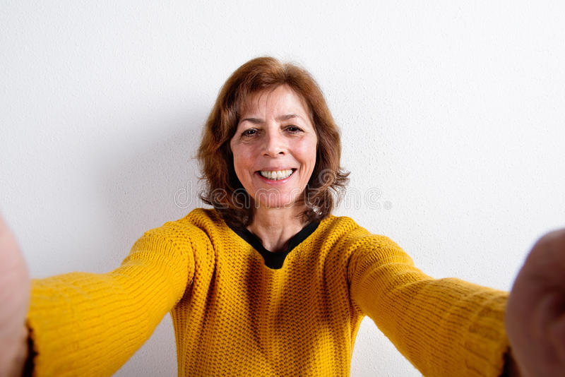 Senior woman in yellow sweater, taking selfie, studio shot. Beautiful happy senior woman in yellow sweater, taking selfie, smiling. Studio shot against white stock image
