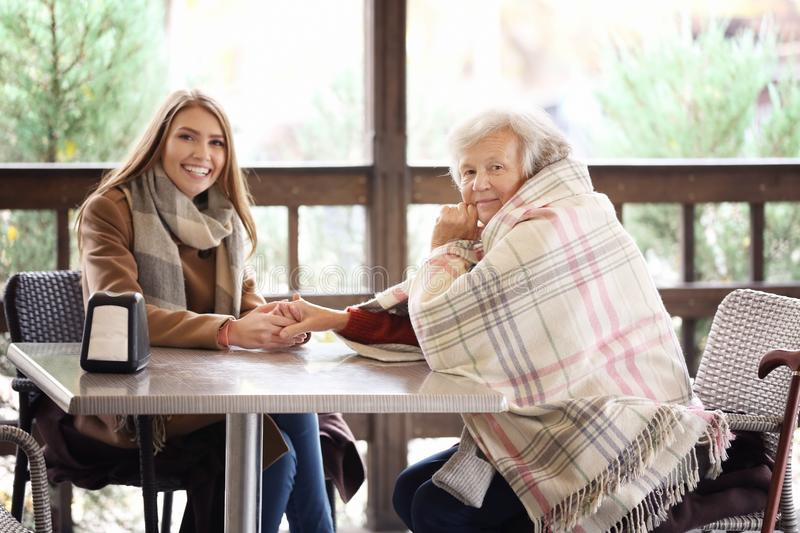 Senior woman and young caregiver sitting at table. Senior women and young caregiver sitting at table in cafe stock images