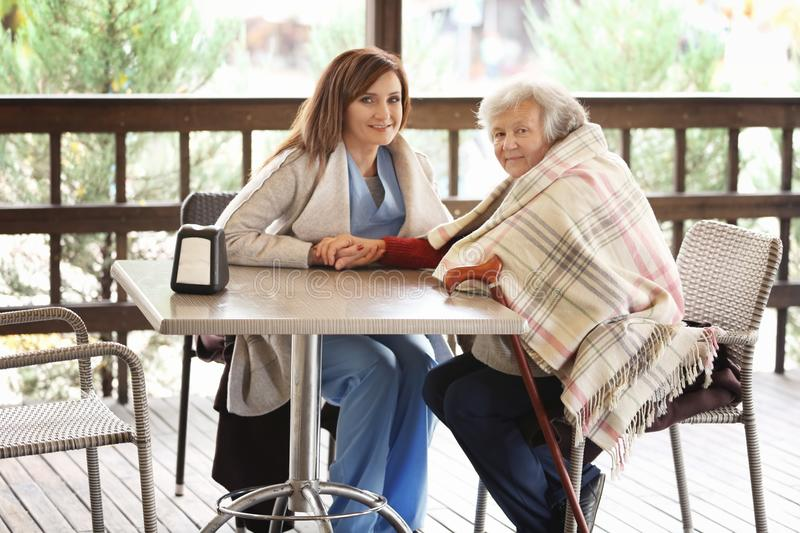 Senior woman and young caregiver sitting at table. Senior women and young caregiver sitting at table in cafe royalty free stock photography