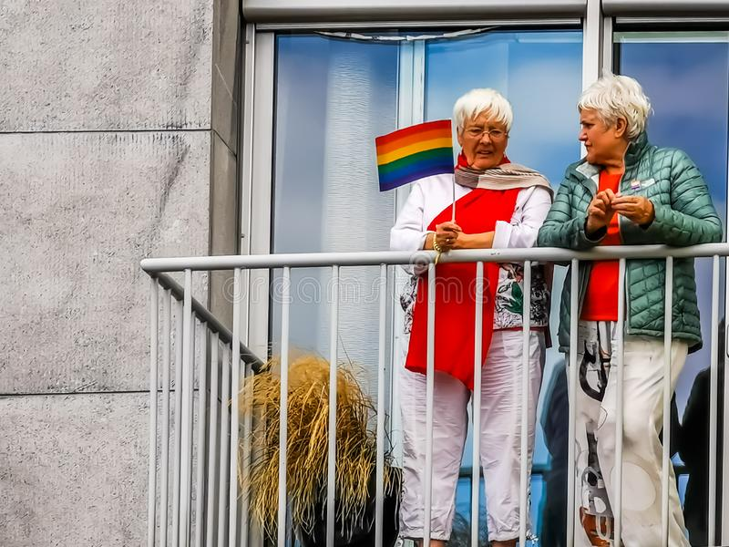 Two senior women on the balcony holding a LGBT rainbow flag, gay pride antwerp, 10 august, 2019, Antwerpen, Belgium. Senior women on the balcony holding a LGBT stock photography