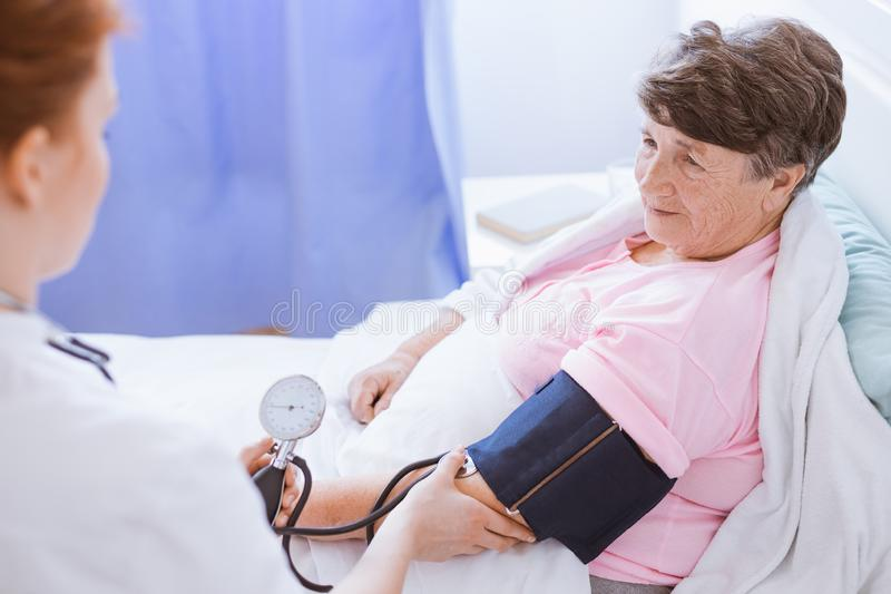 Senior woman with blood pressure monitor on her arm and young intern at hospital stock image