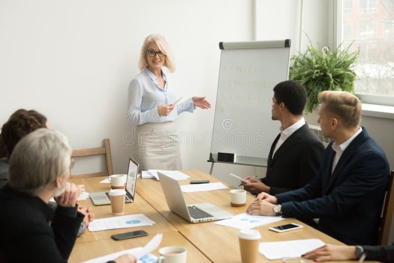 Senior woman boss leading corporate team meeting or giving prese. Senior women boss leading corporate team meeting presenting team goals, smiling aged stock photo