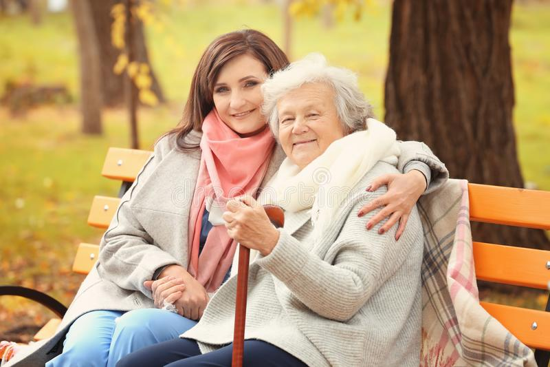 Senior woman with cane and young caregiver sitting on bench. Senior women with cane and young caregiver sitting on bench in park stock photo