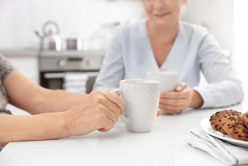 Senior woman and caregiver drinking tea at home. Senior women and caregiver drinking tea at home, closeup stock photography