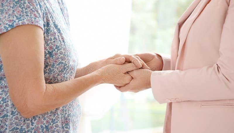 Senior woman and caregiver holding hands at home. Senior women and caregiver holding hands at home, closeup royalty free stock image