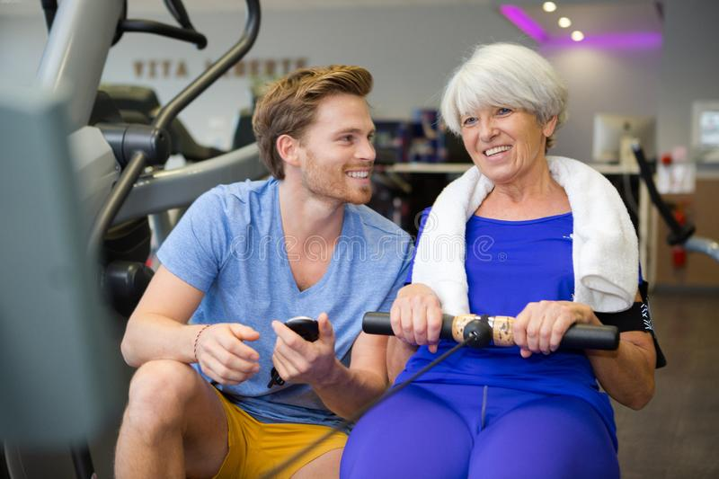 Senior woman doing sport exercises with coach or personal trainer royalty free stock images