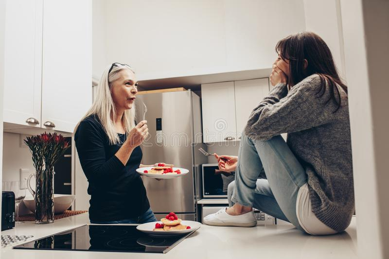 Senior woman eating cookies from a plate standing in kitchen talking to a woman. Two women talking while eating snacks in kitchen royalty free stock photos