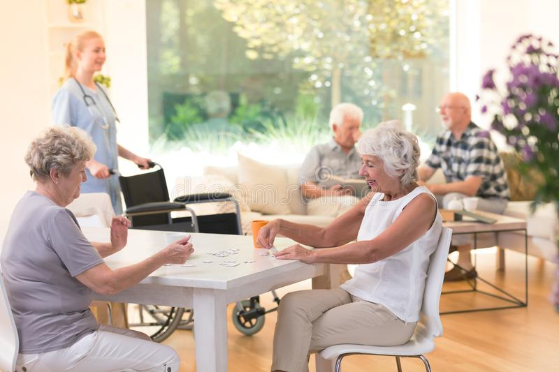 Senior women enjoying time. Senior women enjoying their time together while sitting at a table and doing a puzzle in nursing house stock image