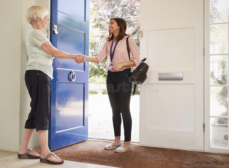 Senior woman greeting female care worker making home visit. Senior women greeting female care worker making home visit royalty free stock photography
