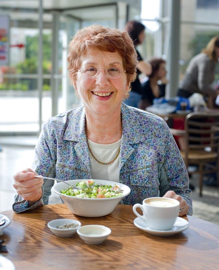 Senior women having salad and coffee stock photography