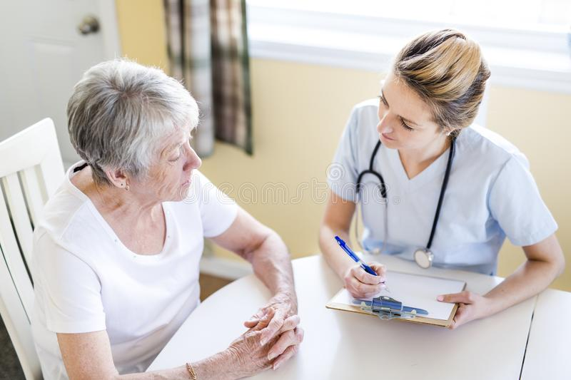 Senior woman with her caregiver at home. A Senior women with her caregiver at home royalty free stock photo