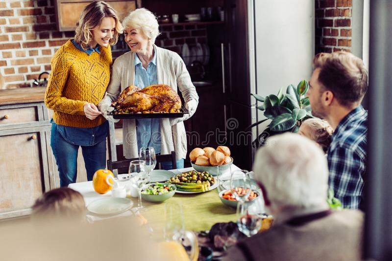 senior woman and her daughter carrying turkey for thanksgiving dinner with their stock photography