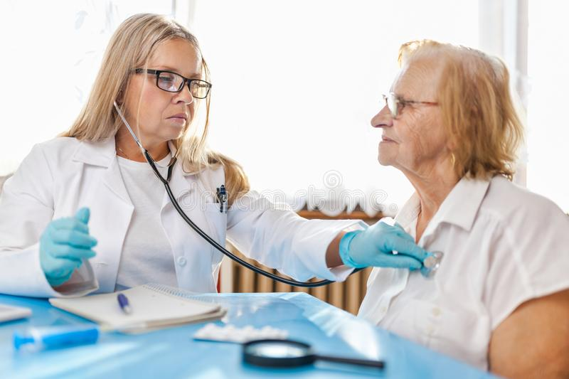 Senior woman during a medical exam with practitioner stock photography