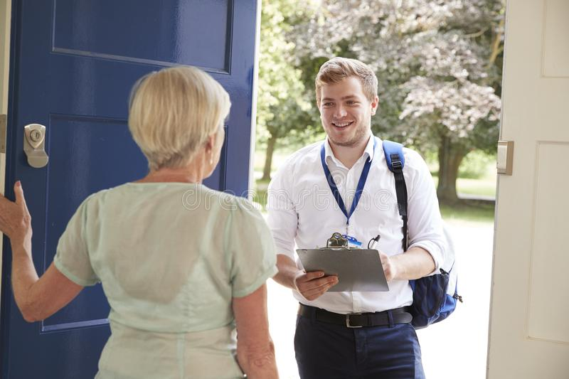 Senior woman opens door to male charity worker doing survey royalty free stock photos