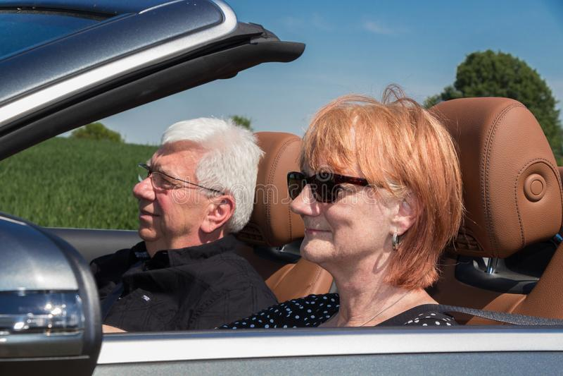 Senior woman with partner driving a car. Senior women with partner driving a car on a sunny day royalty free stock photos