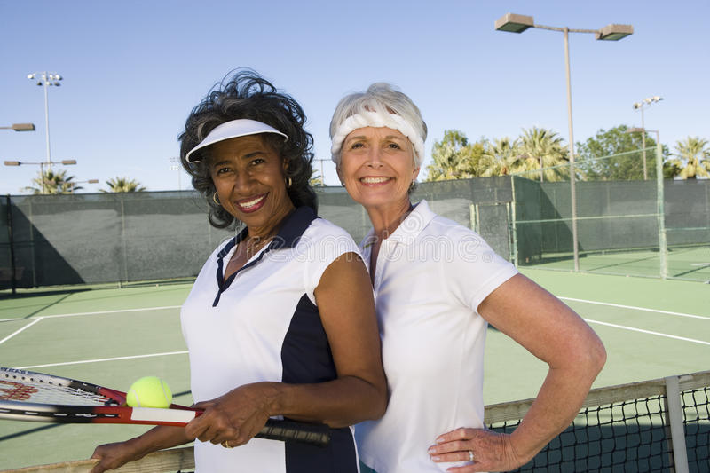 Senior Women Playing Doubles. Portrait of happy senior female tennis players playing doubles royalty free stock images