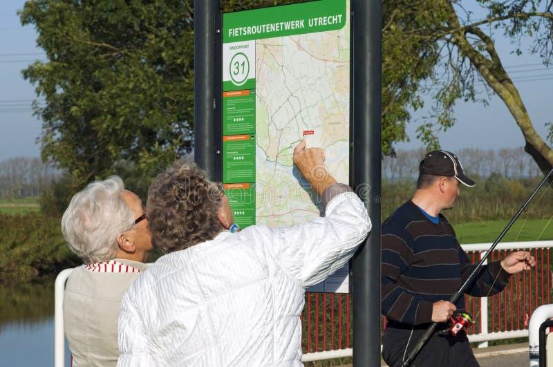 Senior women read map during bike ride stock photos