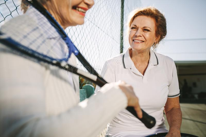 Senior women relaxing after a game of tennis stock photography