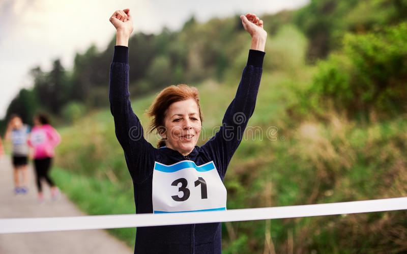 Senior woman runner crossing finish line in a race competition in nature. stock image