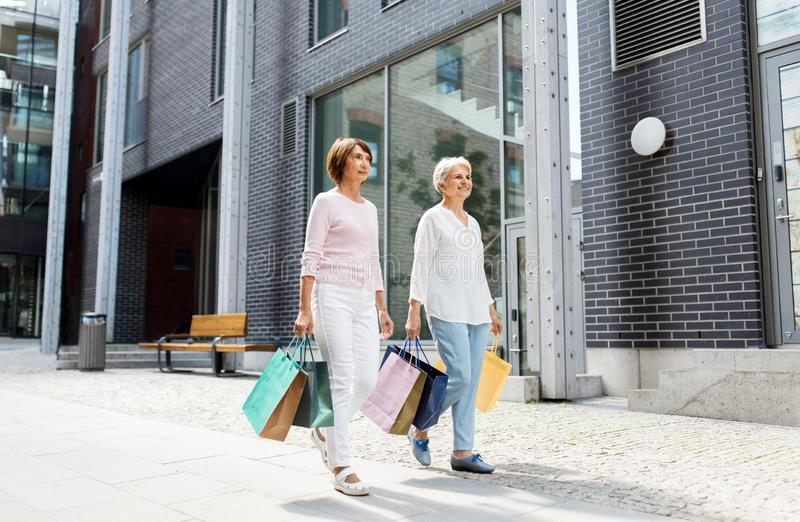 Senior women with shopping bags walking in city stock photography